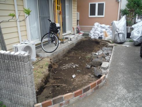 ほぼ、土が掘り出された庭と積まれた土のう袋